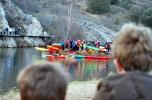 Dos niños observan a los piragüistas en una de las orillas del río