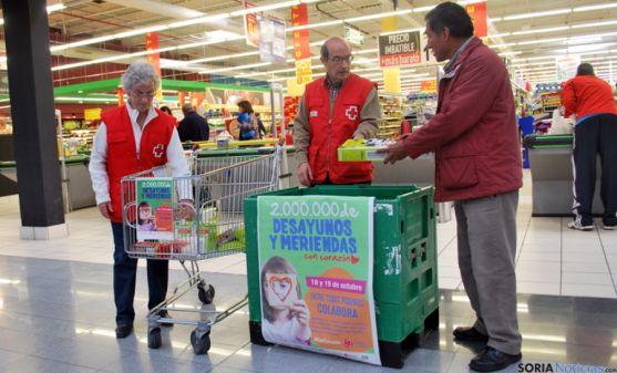 Dos voluntarios recogen alimentos de un donante.