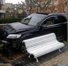 El coche, junto a un banco del paseo