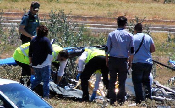 Un momento del levantamiento del cadáver al lado del aparato calcinado por el impacto.