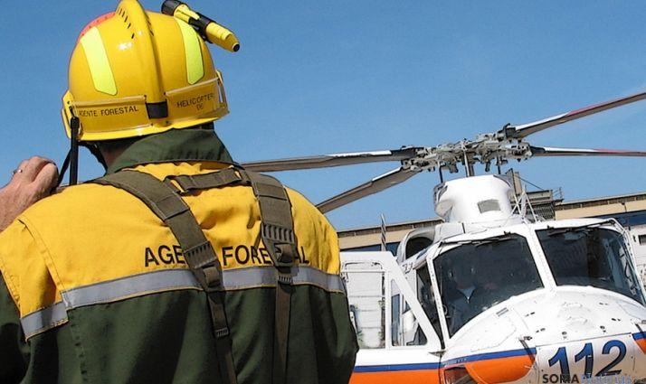 Un agente medioambiental ante un helicóptero del 112.