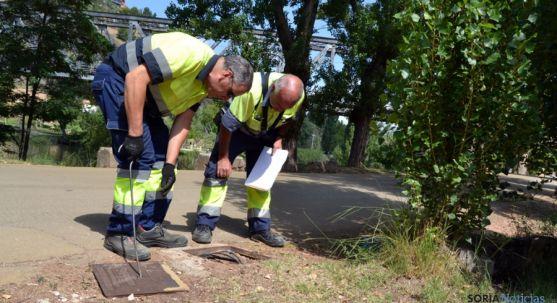 Dos operarios municipales inspeccionan una de las arquetas esta mañana. / SN