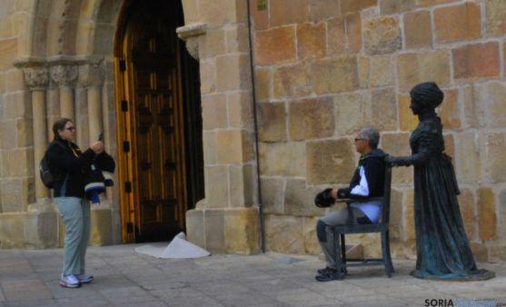 Dos turistas frente a la iglesia de La Mayor y a la estatua de Leonor. / SN