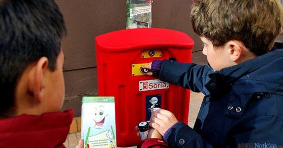 Dos niños depositando pilas en un contenedor. / SN