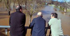 Tres vecinos de Garray observan el río desbordado al paso por la localidad. / SN