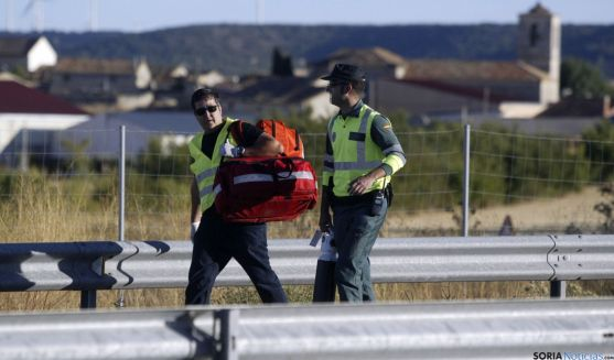 Un sanitario y un agente de la Guardia Civil acudiendo ayer al lugar del accidente. / SN