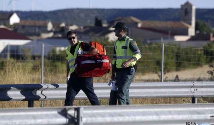 Un sanitario y un agente de la Guardia Civil acudiendo ayer al lugar del accidente. / SN