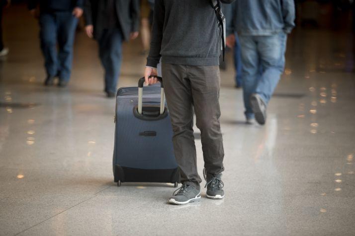 Un viajero arrasatra una maleta. freepik.
