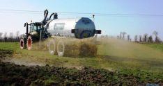 Un tractor y su cisterna de purín en una parcela de cultivo.