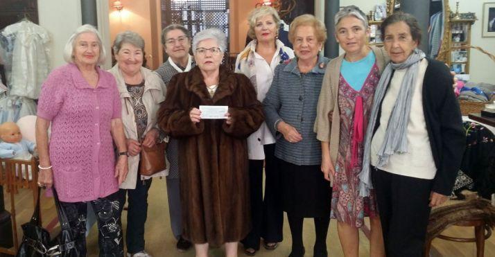 La ganadora, en el centro con la papeleta premiada y el abrigo sorteado.