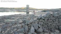 El bajo nivel del pantano deja ver la torre de la iglesia y restos de muros de la localidad de La Muedra, que reaparecen cuando no hay agua.