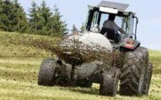 Un tractor esparce purines en un campo.
