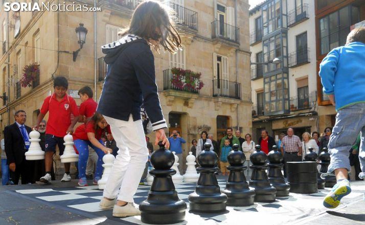 Niños en un ajedrez gigante en la plaza de El Rosel. /SN