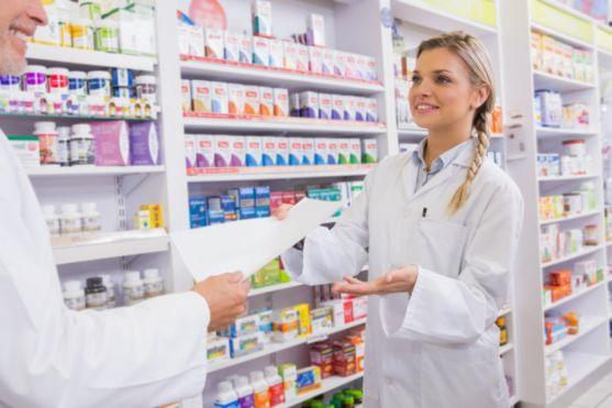 Farmacéutico y aprendiz hablando. Imagen de archivo.