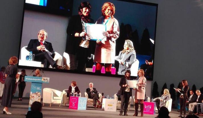 Ana Alegre, en la pantalla a la izquierda, recibe el premio. /Ayto.