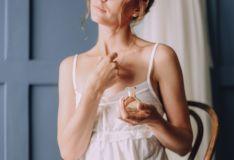 Mujer perfumándose.