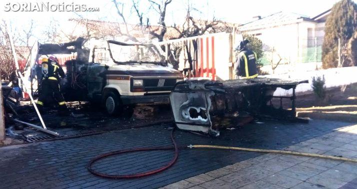 Los bomberos con el vehículo calcinado. /SN