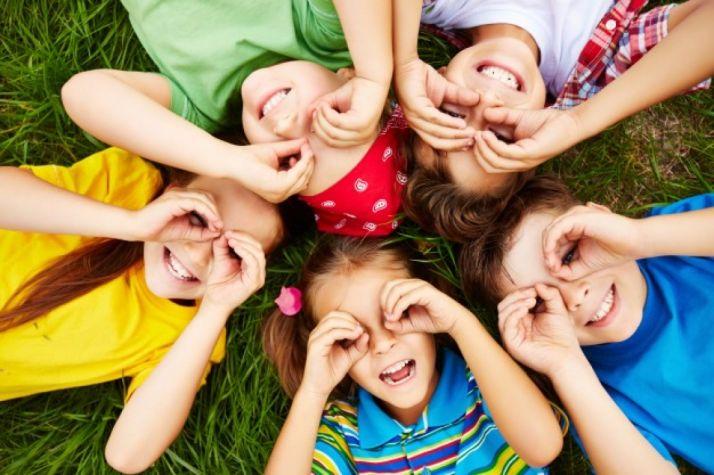 Niños y niñas jugando sobre el césped. Archivo