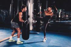 Una dupla (hombre y mujer) practica artes marciales en un gimnasio.
