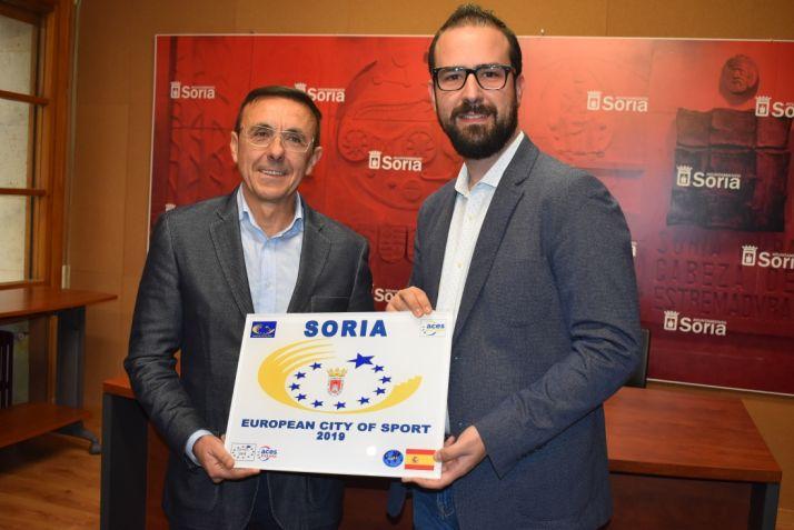 José Hidalgo y Ángel Hernández sujetan una bandera en la que se dibuja 'Soria, Ciudad Europea del Deporte'. Ayuntamiento de Soria