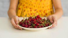 Una niña sostiene un plato de cerezas.
