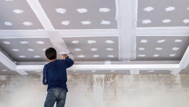 Un albañil instalando placas de yeso laminado.