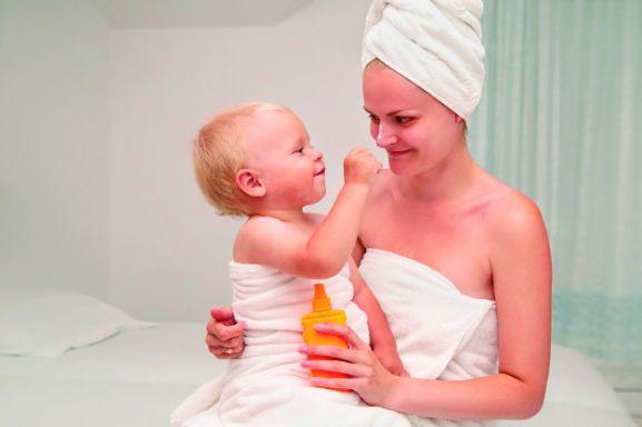 Bebé, sentado en el regazo de su mamá tras salir del baño.