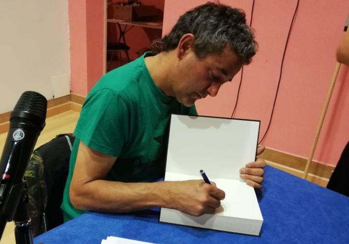 El autor firma un ejemplar de '500 años de rebeldía'