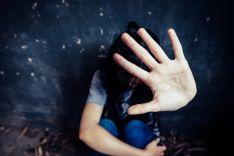 Mujer, arrinconada en una pared y con la mano extendida.