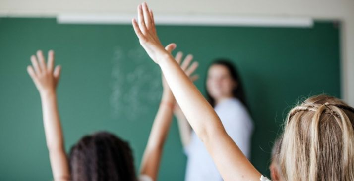 Una profesora atiende las dudas de los alumnos.