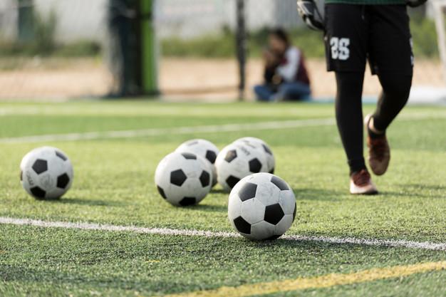 Campo de fútbol y balones sobre el verde.