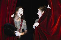 Dos mimos detrás de una cortina roja.