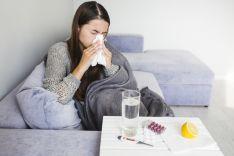 Mujer resfriada en el sofá.