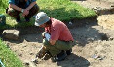 Un joven en un campo de voluntariado arqueológico en CyL.