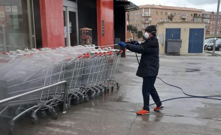 Un operario de limpieza en el exterior de un supermercado en Almazán.