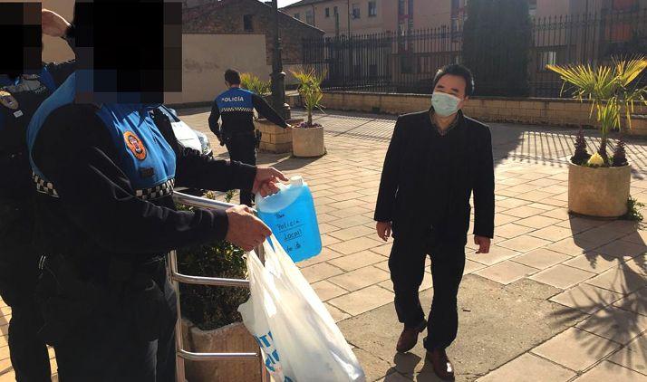 Un miembro de la comunidad china en la entrega de los productos. /Ayto.