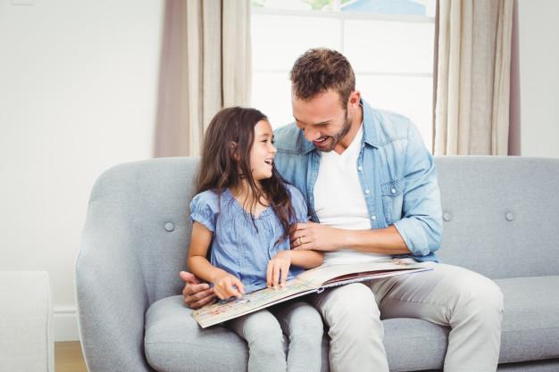 Un padre y su hija leen un cuento en casa.