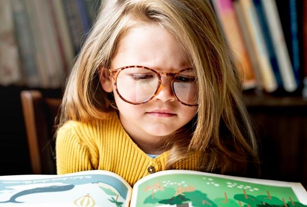 Una pequeña lee un cuento en casa.
