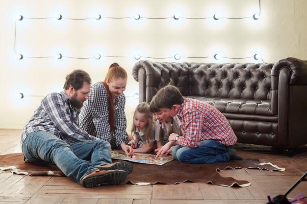 Familia de cinco miembros jugando en su hogar.