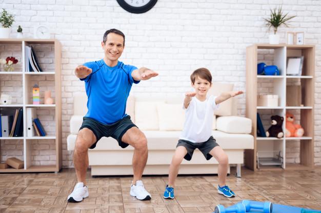 Padre e hijo disfrutan de una sesión de ejercicio en casa.