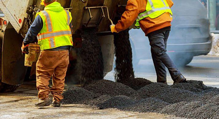 Dos operarios realizan labores de asfaltado.