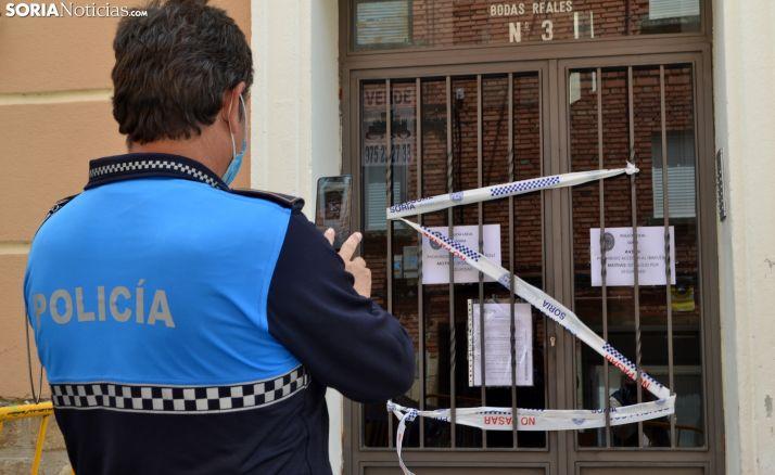Un agente de la Policía Local ante uno de los portales del edifcio. /SN
