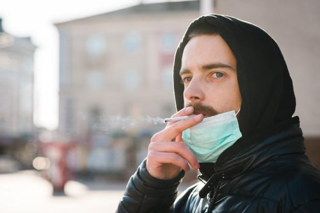 Hombre se baja la mascarilla para fumar en la calle.