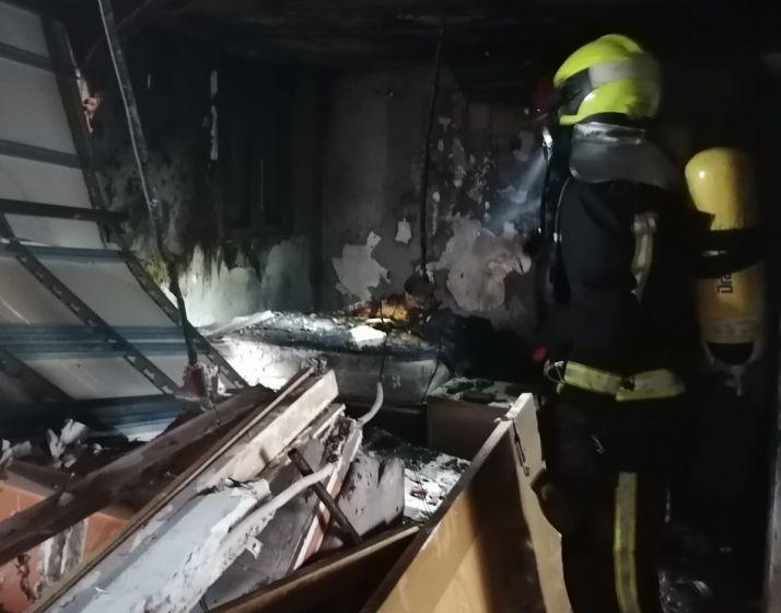 Un bombero trabaja en la vivienda que ha sufrido la explosión.