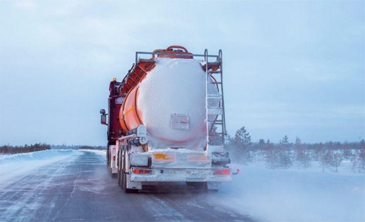 Un vehículo articulado circulando por una carretera convencional tras una nevada.
