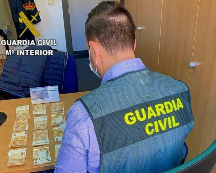 Guardia Civil con parte del dinero recuperado.