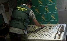 Un agente de la Guardia Civil con algunos de los objetos confiscados. /GC